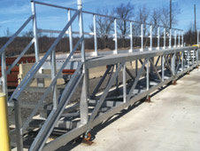 GREEN Flatbed Access Platforms | Roll-Track Design Allows for Varying Trailer Widths & Easier Trailer Placement